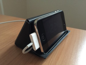The small black box that holds the iPhone manual is a perfect stand